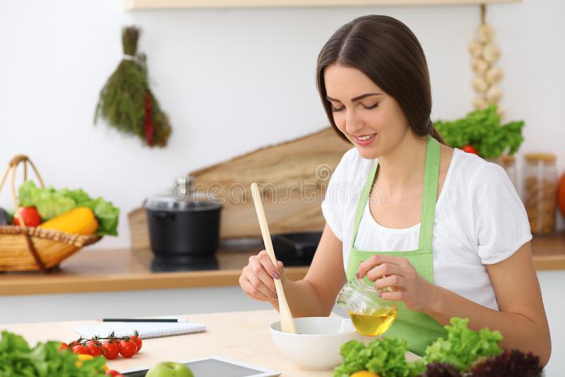 Härlig latinamerikan eller latin - den amerikanska kvinnan är den hållande träskeden, medan laga mat i köket royaltyfria foton