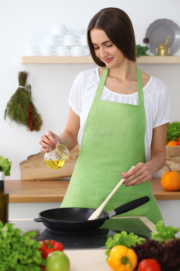 Härlig latinamerikan eller latin - den amerikanska kvinnan är den hållande träskeden, medan laga mat sallad i köket royaltyfria foton