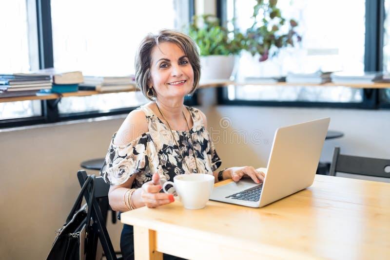 Härlig latinamerikansk kvinna på kafét med bärbara datorn arkivbild