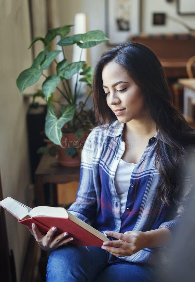 Härlig latinamerikansk kvinna som läser en pappers- bok fotografering för bildbyråer