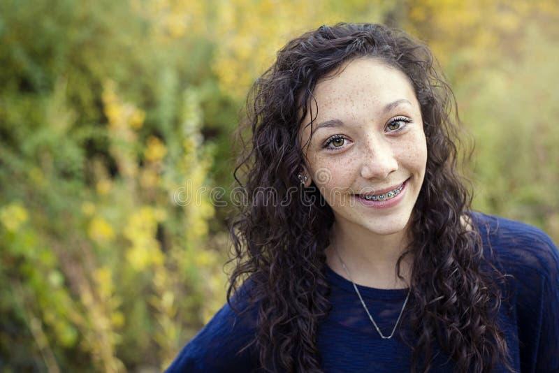 Härlig latinamerikansk tonårig flickastående med hänglsen royaltyfria bilder