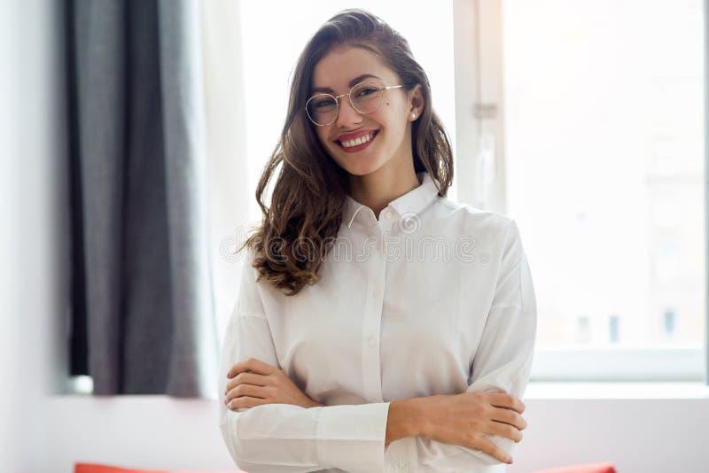 Härlig le affärskvinna med glasögon som ser kameran i hotellrummet royaltyfri foto
