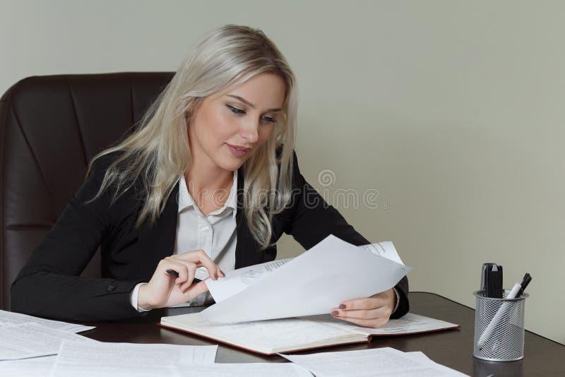 Härlig le affärskvinna som arbetar på hennes kontorsskrivbord med dokument royaltyfri bild