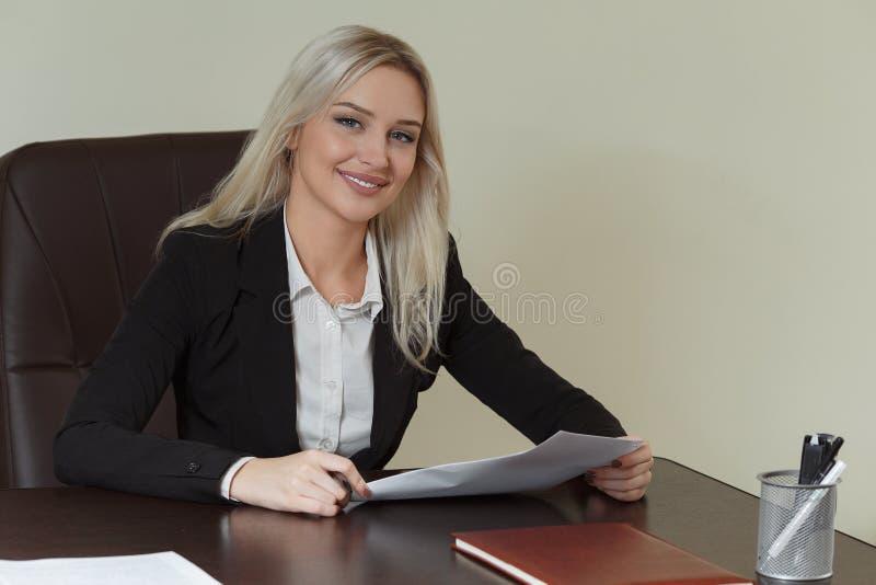 Härlig le affärskvinna som arbetar på hennes kontorsskrivbord med dokument royaltyfri fotografi