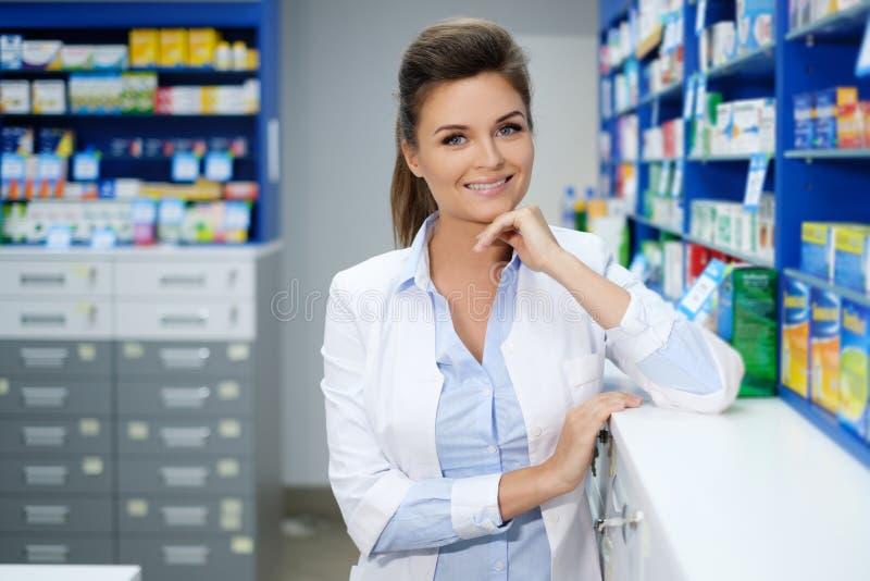 Härlig le apotekare för ung kvinna som gör hans arbete i apotek arkivfoto