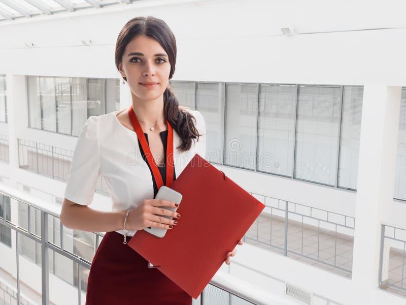 Härlig le bakgrund för affärskvinnaStanding Against White kontor Stående av affärskvinnan med en mapp i henne händer royaltyfri bild