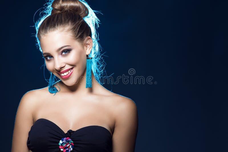 Härlig le blåögd ung flicka med det perfekta sminket som bär svarta axelbandslösa behå- och blåtttofsörhängen arkivfoton