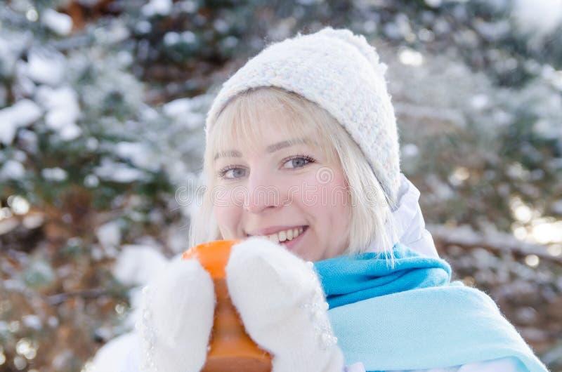Härlig le blond flicka i en sporthatt som rymmer en kopp av varmt te arkivbilder
