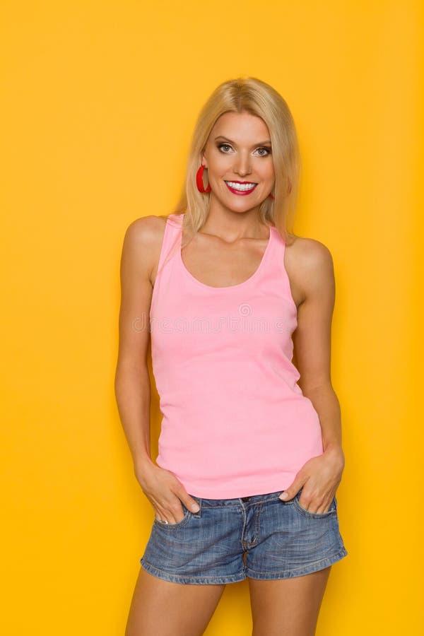 Härlig le blond kvinna i rosa ärmlös tröja- och jeanskortslutningar fotografering för bildbyråer