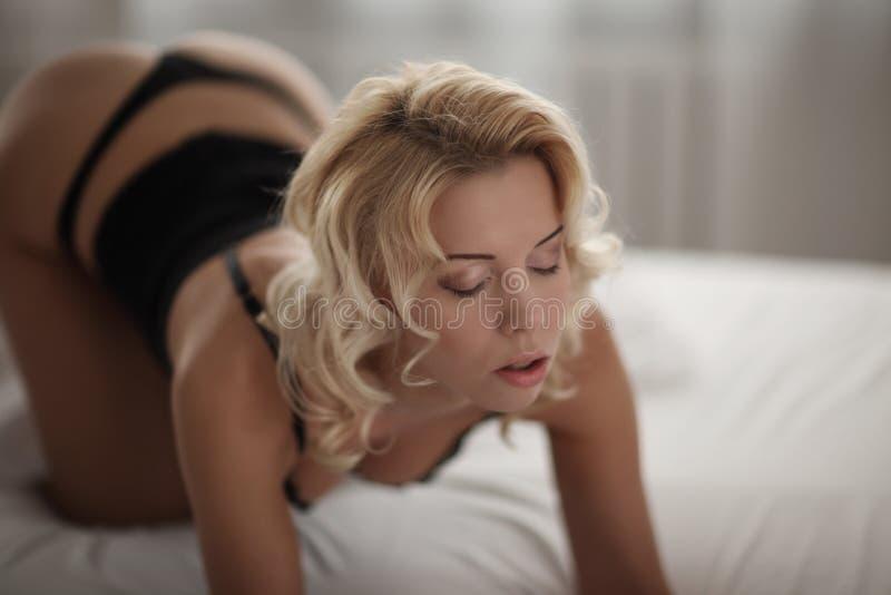 Härlig le blond kvinna med länge slanka ben som poserar sovrummet royaltyfria foton