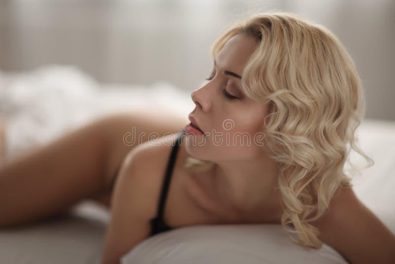 Härlig le blond kvinna med länge slanka ben som poserar sovrummet arkivfoton