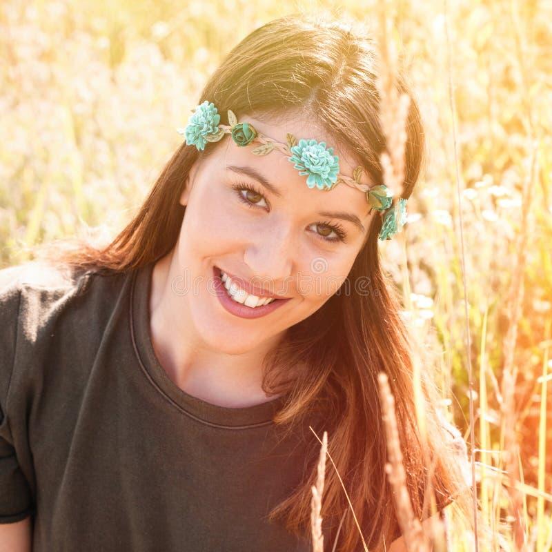 Härlig le bohostående för ung kvinna med huvudmusikbandet med blommor i sommaräng royaltyfri fotografi