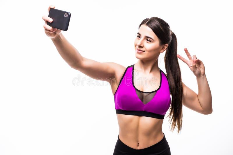 Härlig le färdig idrottskvinna som tar en selfie och visar fredgest, medan stå över vit bakgrund royaltyfri fotografi