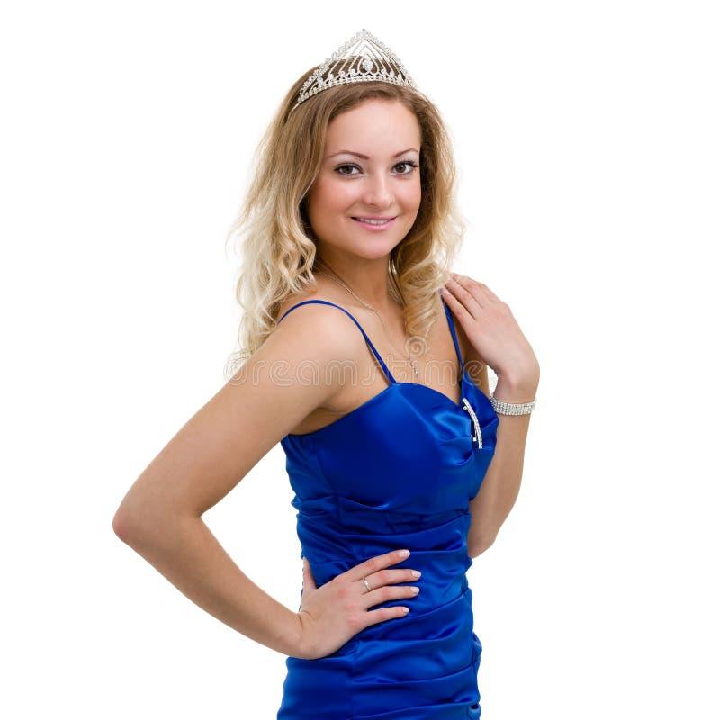 Härlig le flicka i en blå klänning med diademen på en vit royaltyfria bilder