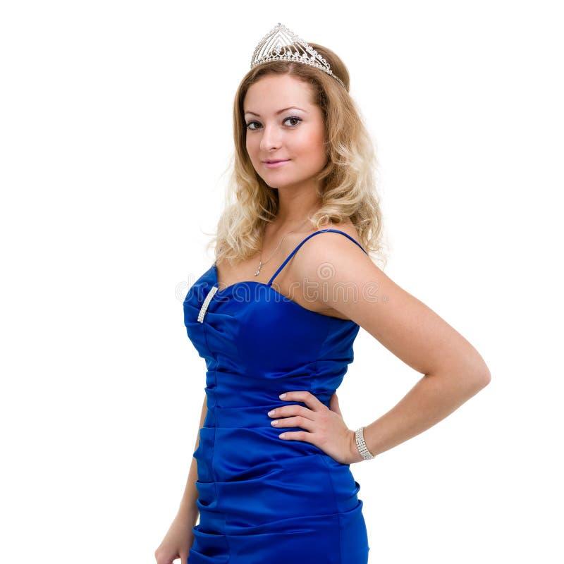 Härlig le flicka i en blå klänning med diademen på en vit royaltyfri foto