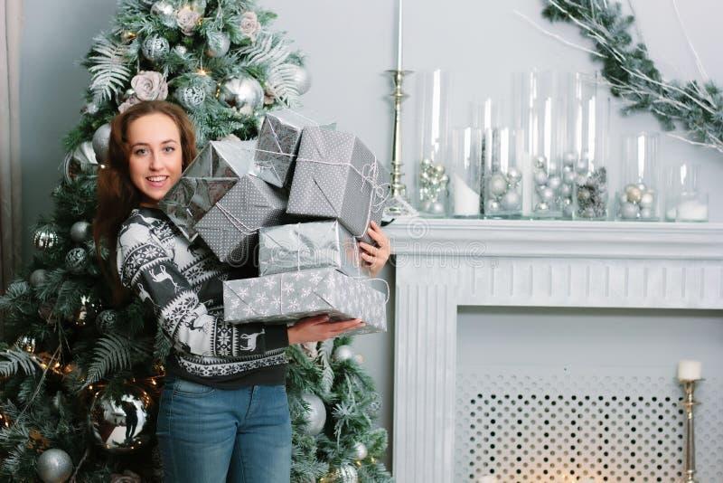 Härlig le flicka med en hög av gåvor nära julträdet royaltyfri foto