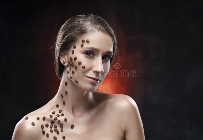 Härlig le flicka med nakna skuldror Kaffebönor klibbades artistically till den sunda rena huden av hennes framsida och hals royaltyfri foto