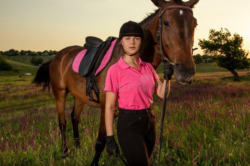 Härlig le flickajockeyställning bredvid hennes bruna häst som bär den speciala likformign på en himmel och en grön fältbakgrund arkivfoton