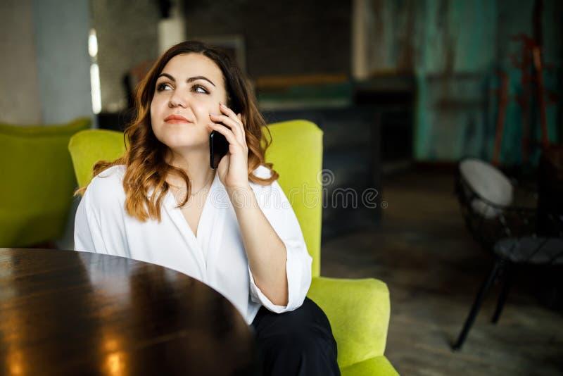 Härlig le iklädd klänning för ung kvinna som sitter i stol på kafét som talar på mobiltelefonen, stilfull inre arkivbild