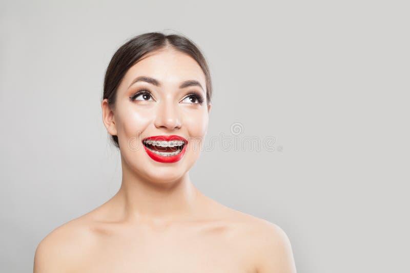 Härlig le kvinna i hänglsen på vit Lycklig flicka med hänglsenståenden arkivfoton