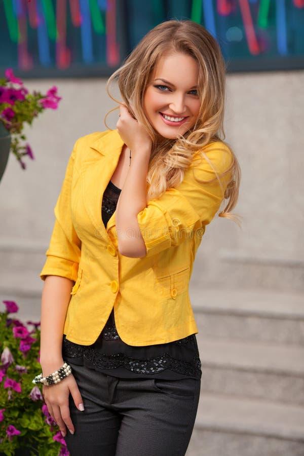 Härlig le kvinna med att posera för gult omslag som och för blont hår är utomhus- fashion flickan arkivbild