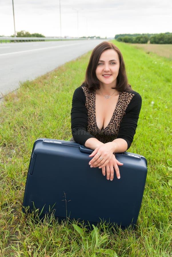 Härlig le kvinna med resväskan royaltyfria bilder