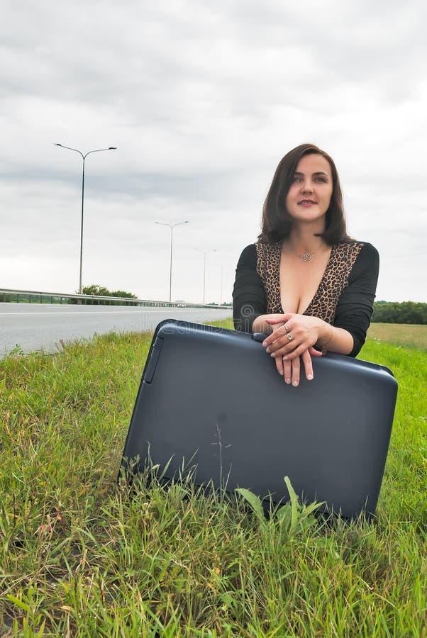 Härlig le kvinna med resväskan fotografering för bildbyråer