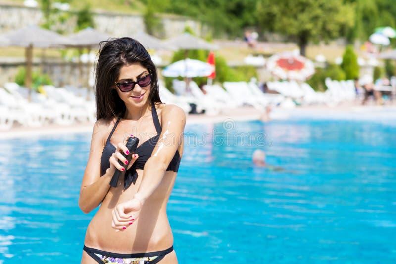Härlig le kvinna som applicerar sol-skydd kräm arkivbilder