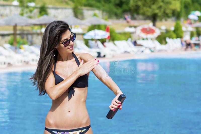 Härlig le kvinna som applicerar sol-skydd kräm arkivbild