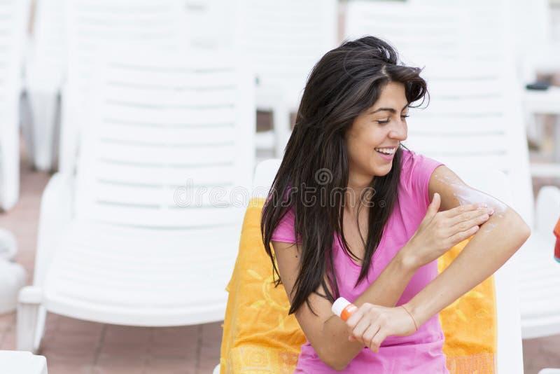 Härlig le kvinna som applicerar sol-skydd kräm arkivfoto