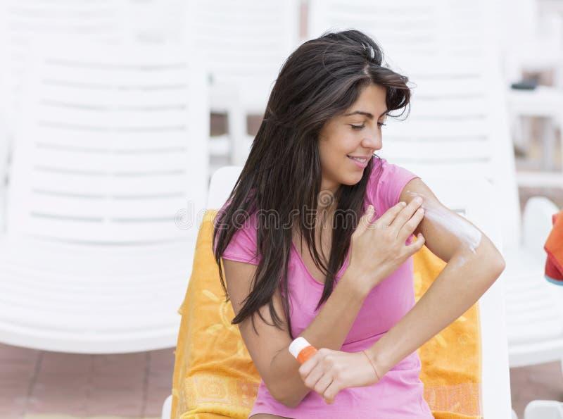 Härlig le kvinna som applicerar sol-skydd kräm fotografering för bildbyråer