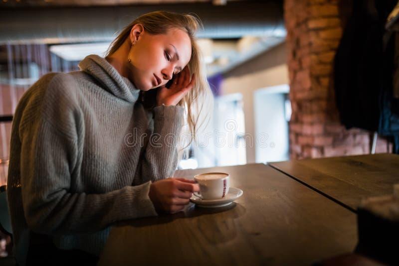 Härlig le kvinna som dricker kaffe på kafét Stående av den mogna kvinnan i en kafeteria som dricker varm cappuccino och ser ca arkivbilder