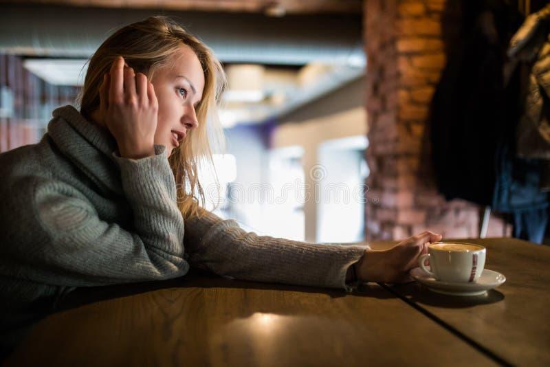 Härlig le kvinna som dricker kaffe på kafét Stående av den mogna kvinnan i en kafeteria som dricker varm cappuccino och ser ca royaltyfri foto