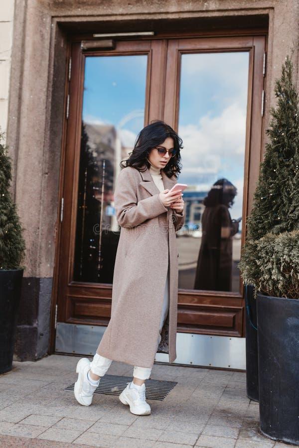 Härlig le kvinna som går på stadsgatan från arbete med kaffekoppen och smsar på mobiltelefonen arkivfoton