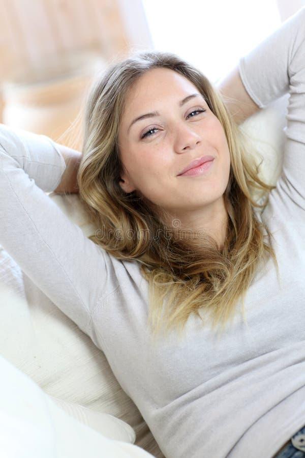 Härlig le kvinna som kopplar av i soffan arkivfoton