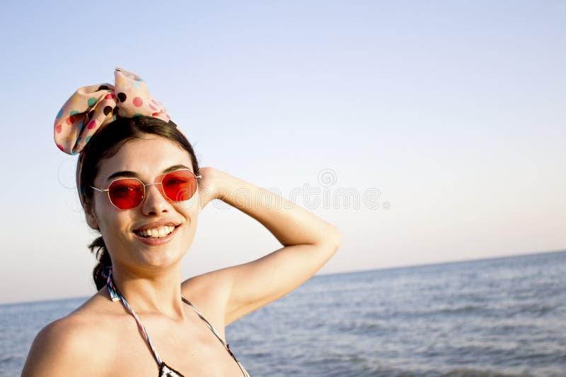 Härlig le kvinna som ser kameran på stranden arkivfoto