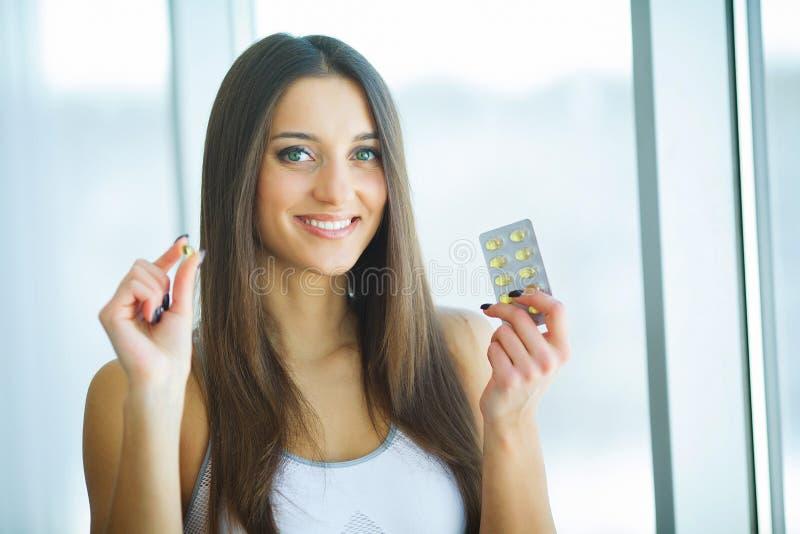 Härlig le kvinna som tar vitaminpreventivpilleren Dietary supplement royaltyfria foton