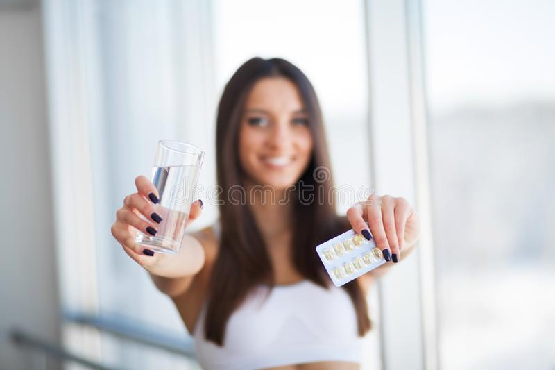 Härlig le kvinna som tar vitaminpreventivpilleren Dietary supplement arkivbild