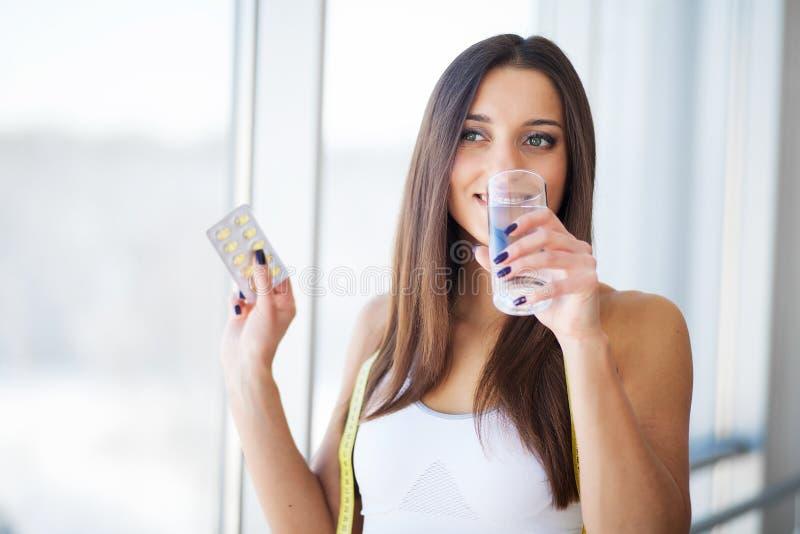 Härlig le kvinna som tar vitaminpreventivpilleren Dietary supplement arkivfoto