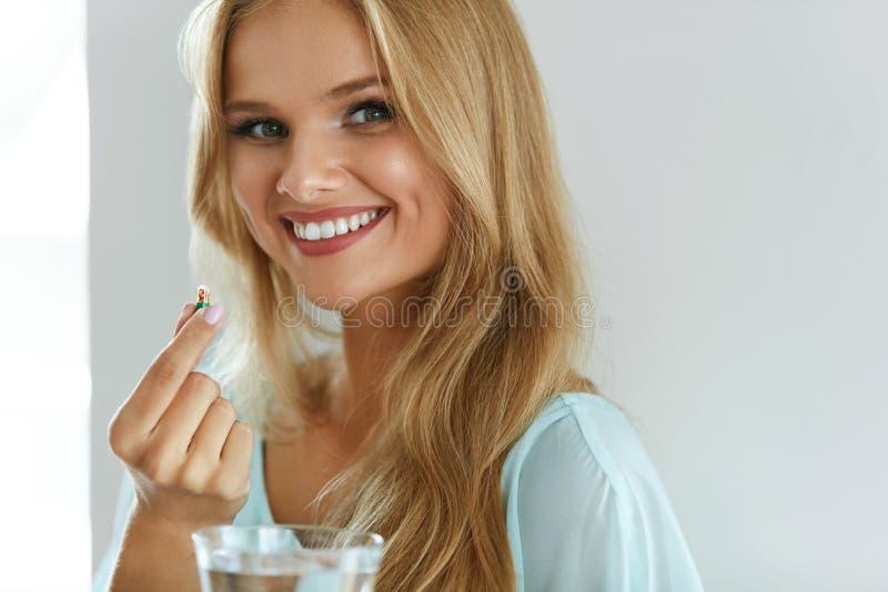 Härlig le kvinna som tar vitaminpreventivpilleren Dietary supplement royaltyfria bilder