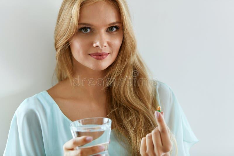 Härlig le kvinna som tar vitaminpreventivpilleren Dietary supplement fotografering för bildbyråer