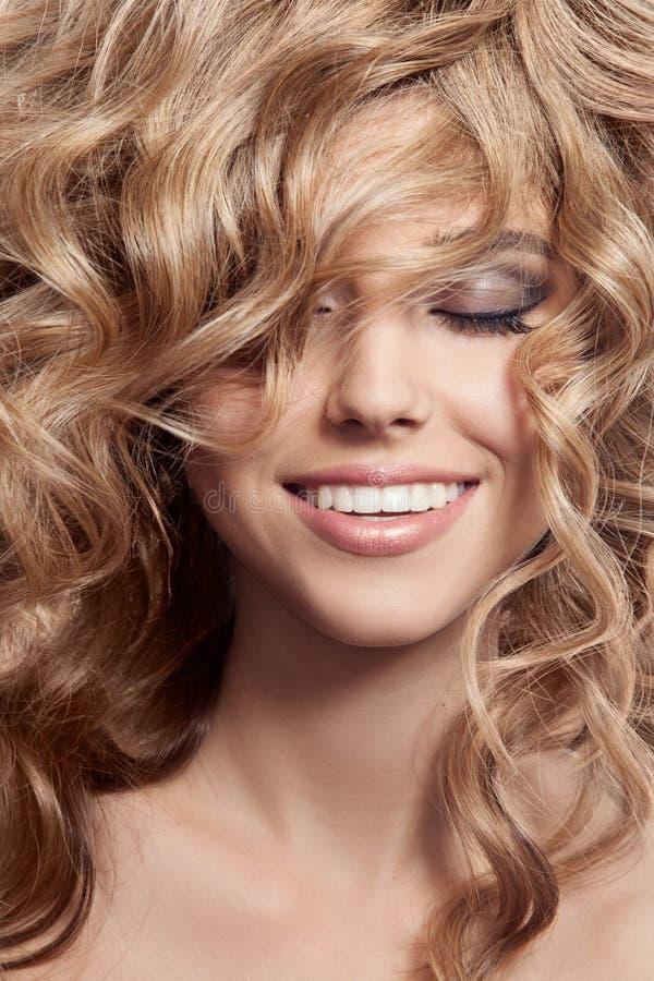 Härlig le kvinna. Sunt långt lockigt hår arkivbilder