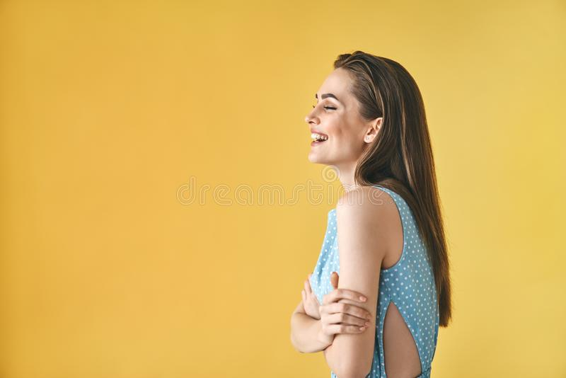 Härlig le kvinnaprofilstående på gul bakgrund med kopieringsutrymme arkivfoton