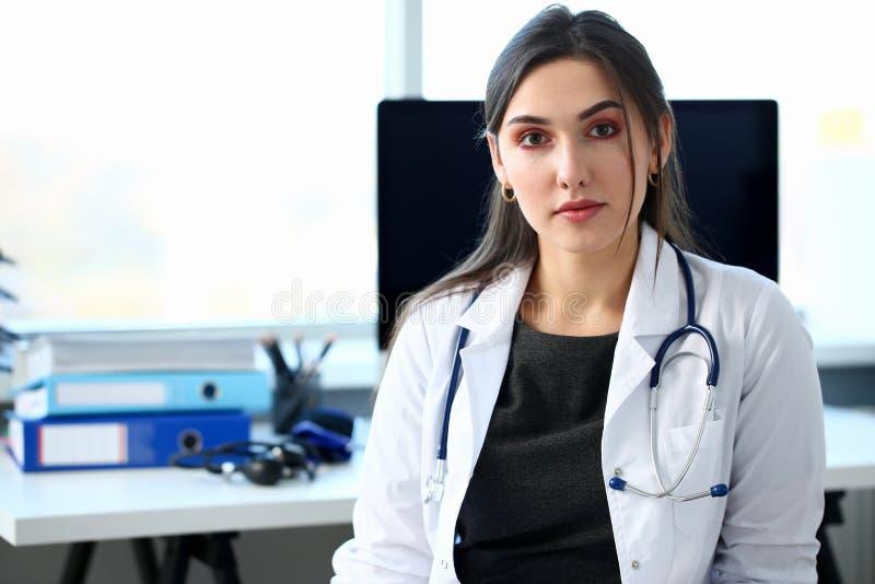 Härlig le kvinnlig doktor på arbetsplatsståenden arkivfoto