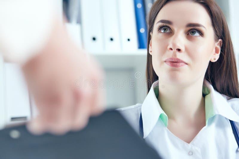 Härlig le kvinnlig medicindoktor som lyssnar försiktigt tålmodiga klagomål i medicinskt kontor Medicinsk vård eller royaltyfri foto