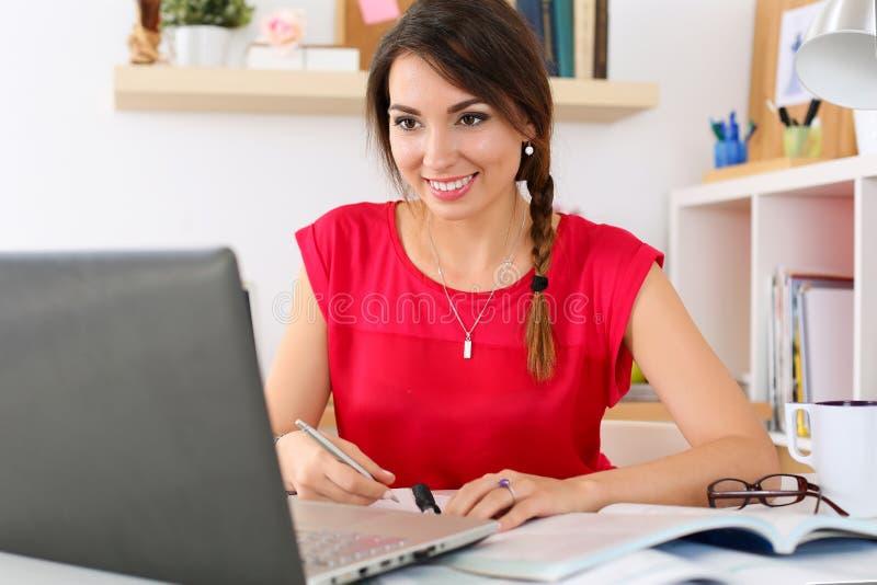 Härlig le kvinnlig student som använder online-utbildningsservice arkivbilder