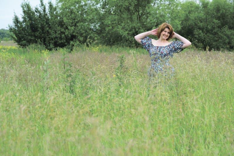 Härlig le medelålders kvinna i natur i sommar arkivbilder