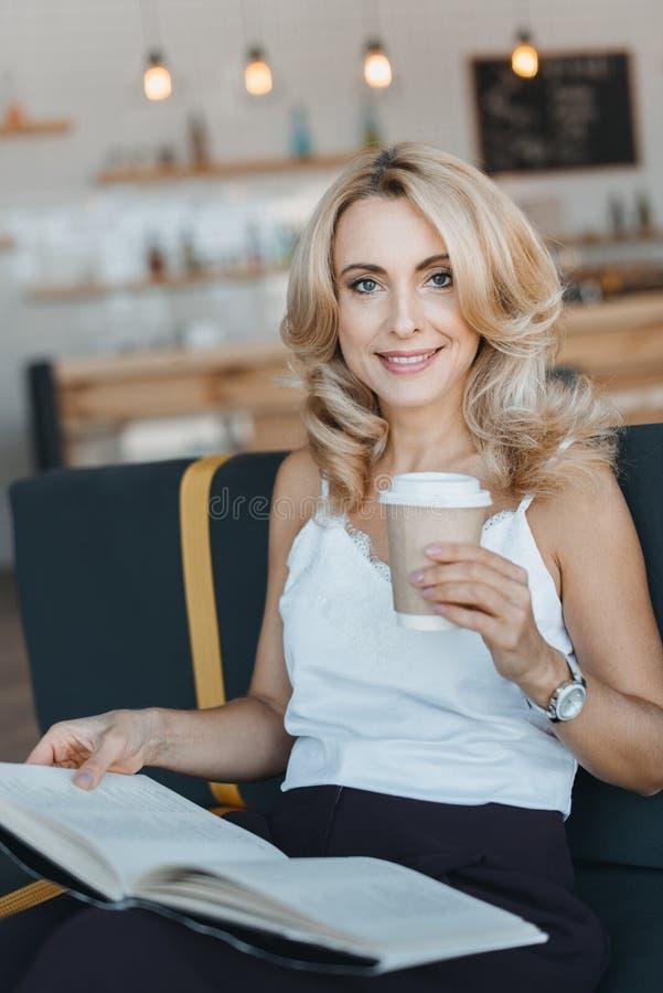 härlig le mogen kvinnaläsebok och drickakaffe royaltyfria bilder