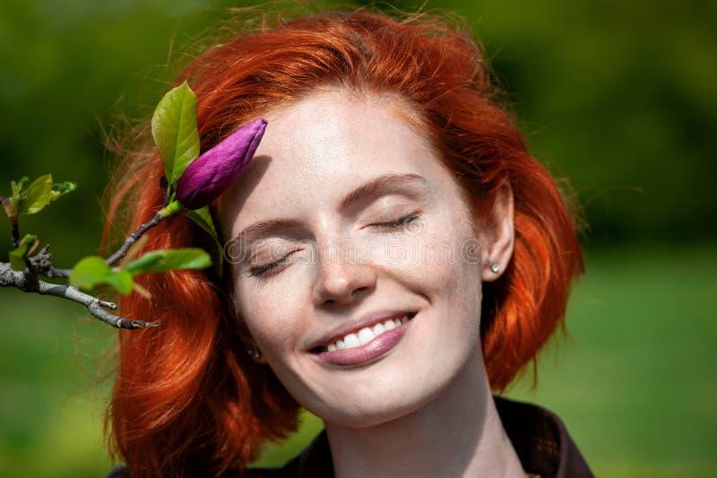 Härlig le röd haired flicka med stängda ögon tycka om mjukheten av magnolian för blommaknopp f inomhus arkivfoton