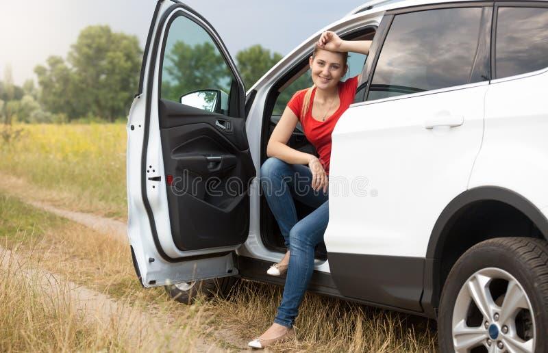 Härlig le resande för ung kvinna med bilen på countrysideevägen fotografering för bildbyråer